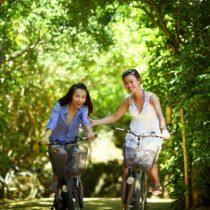 Girls biking in Denver park | Going carless | Vita Apartment Locators